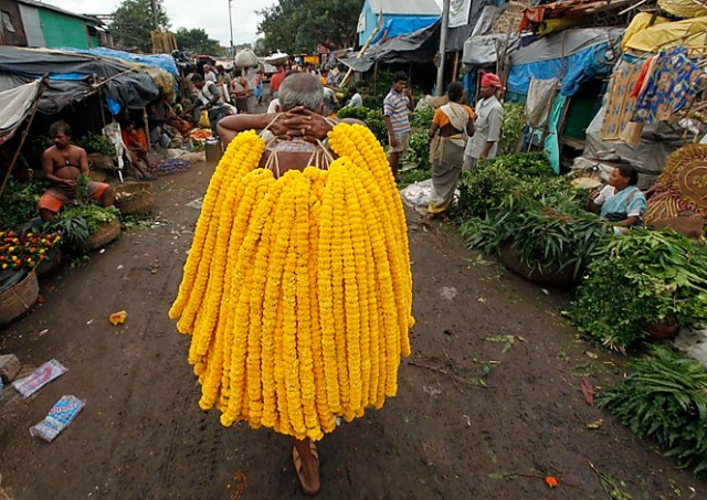 "A vendor sells garlands of marigold flowers at a wholesale flower market ahead of ""Janamashtmi"", in Kolkata"