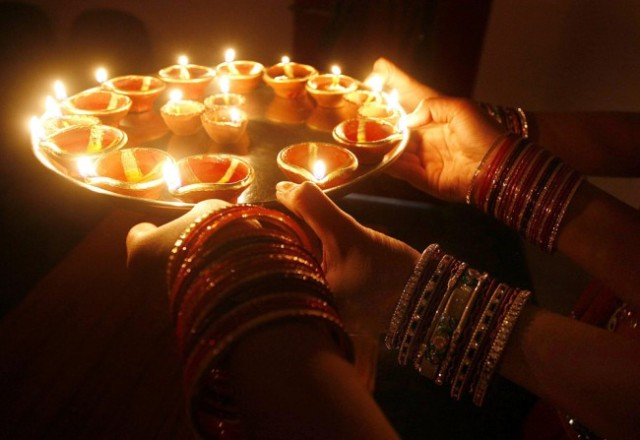 Indian-girls-hold-earthen-lamps-on-the-occasion-of-Dhanteras-ahead-of-the-Diwali-festival-in-Bhopal-India-late-night-on-Nov.-11.-The-word-Dhan-means-wealth-and-the-day-before-the-Diwali-festival-has-a-grea